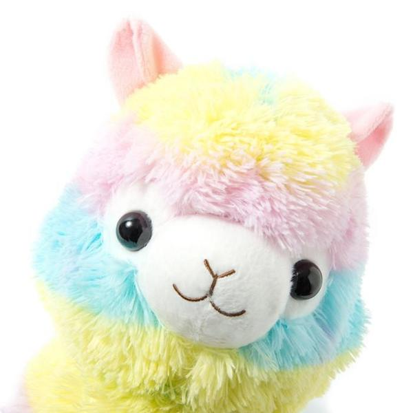 A plush rainbow alpaca head is peeking out with a small smile on its face.